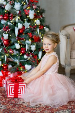 little girl with Christmas gift sitting near tree