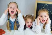 tři mladé školačky u stolu