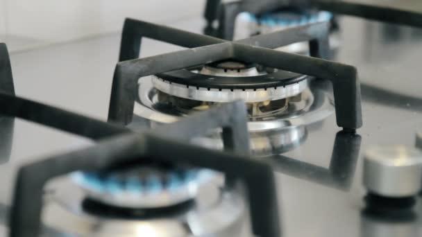 Zapalování hořáků plynu na sporáku v kuchyni
