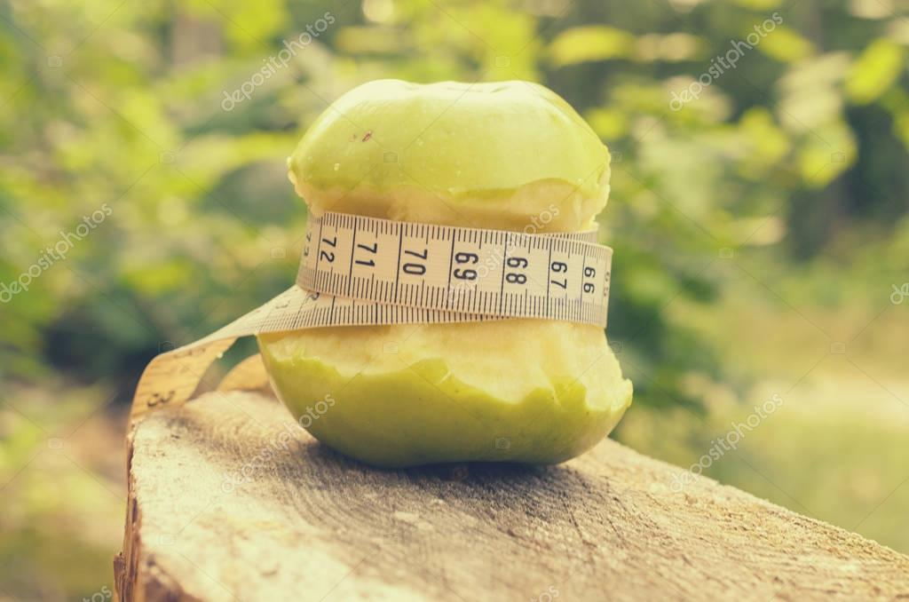 A green apple with a green ribbon and a measuring tape.