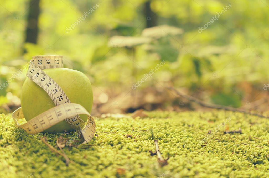 Green apple on green grass with measuring tape and without.