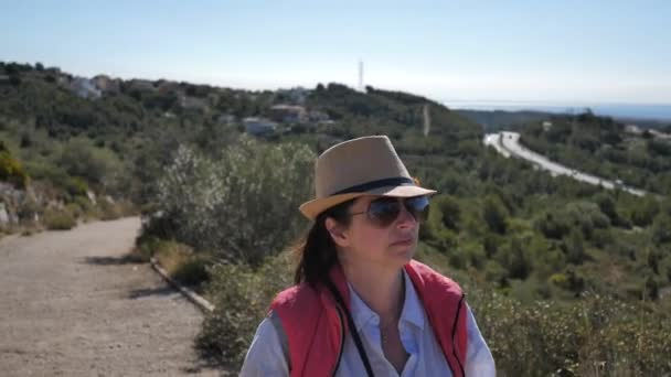 woman in a hat and sunglasses walks on top of a mountain, looks around