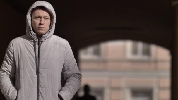portrét seriózního muže v kapuci v zimě při pohledu do kamery