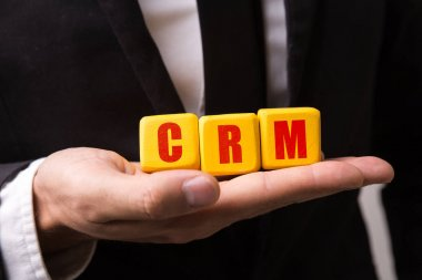 Hand holding a cube with the text: CRM (Customer Relationship Management)