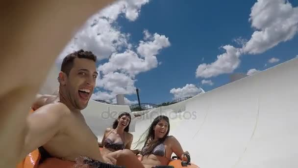 Friends having fun and sliding down in a water slide