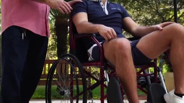 Otec, podporovat jeho zdravotně postiženého syna na invalidním vozíku v parku