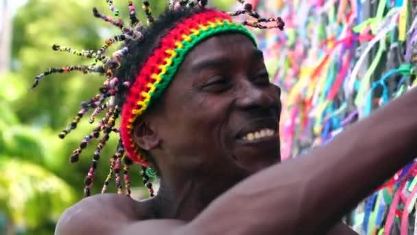 Brazil making a kívánságát, (Fita do Bonfim) brazil szalagokkal, a templom kerítésén, Salvador, Bahia, Brazília