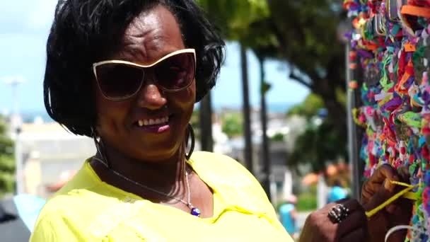 Donna che fa un desiderio con nastri brasiliani (Fita do Bonfim) sulla Chiesa di Bonfim recinzione in Salvador, Bahia, Brasile