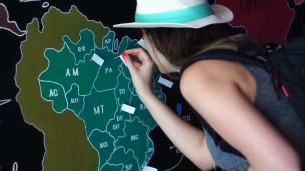 Donna viaggiatore mettendo Pin posizione dei paesi viaggiatori la mappa