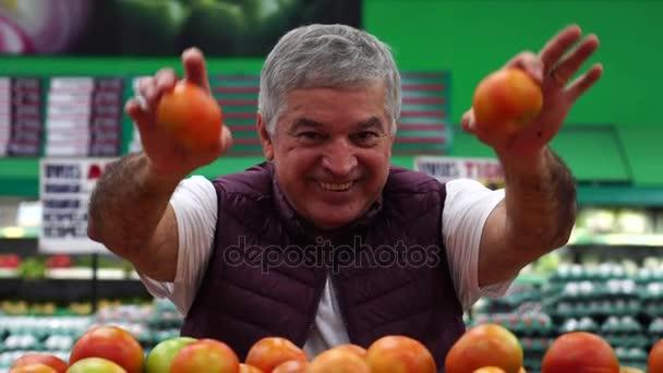 Muž výběru a zobrazení rajčata v supermarketu