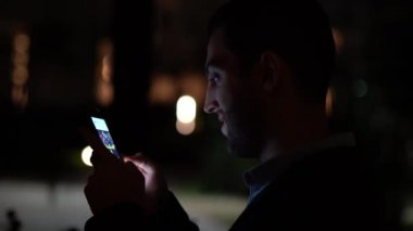 Business man using mobile at nighttime