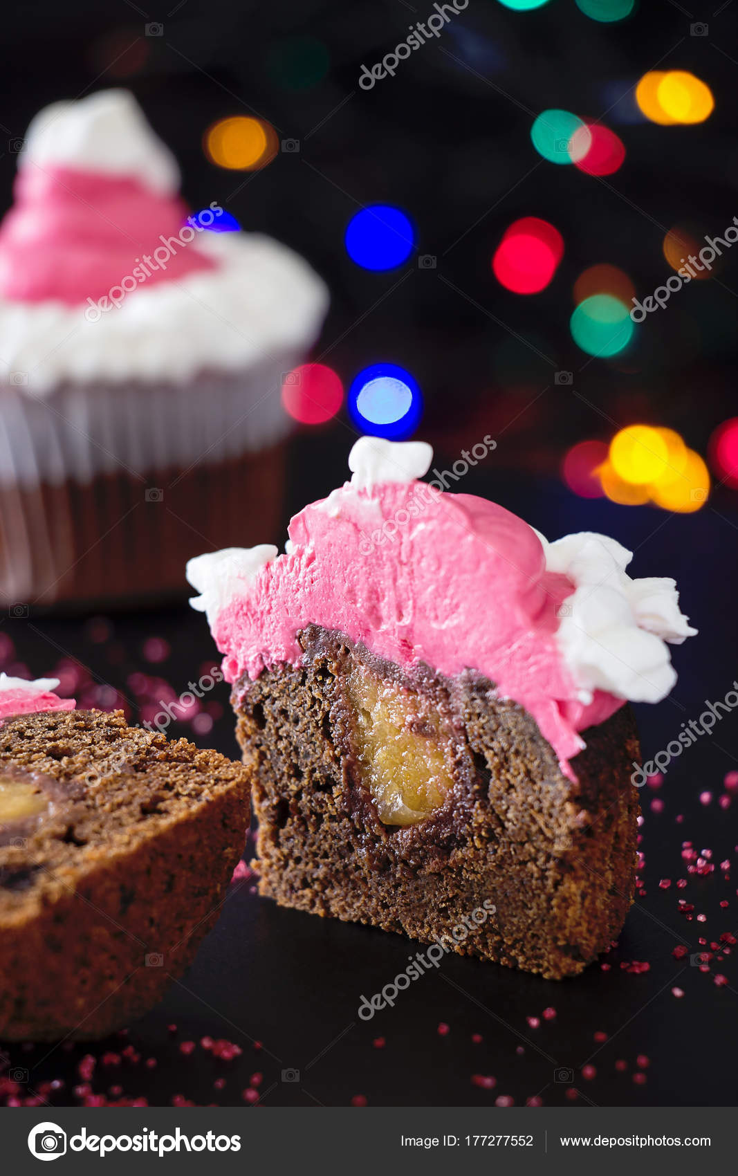 Half of Christmas homemade chocolate cupcake with pink cream cheese frosting. Blur light and dark background. Selective focus. — Photo by alju