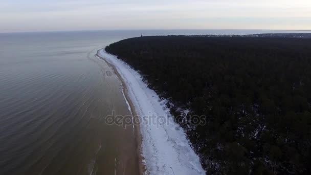 Luftaufnahmen von Drohnen, die über zugefrorenen Strand und offenes Meer fliegen und dabei Wellen zermalmen