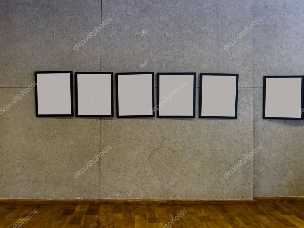 exhibition hall with concrete walls and empty picture frames