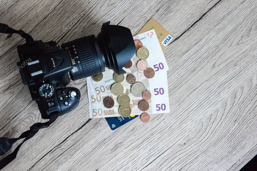 photographic camera with money euro and visa vard on wooden tabl
