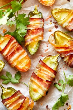 Jalapeno poppers wrapped in bacon stuffed with cheese seasoned with herbs and spices, delicious starter