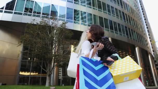 Dvě mladé dívky stojící na ulici nedaleko nákupního centra s obchody, dr¾te telefon, objímání, líbání a směje se