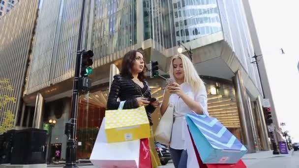 Dvě dívky se spoustou nákupů jsou velké budovou na semaforech. Další projíždějících aut