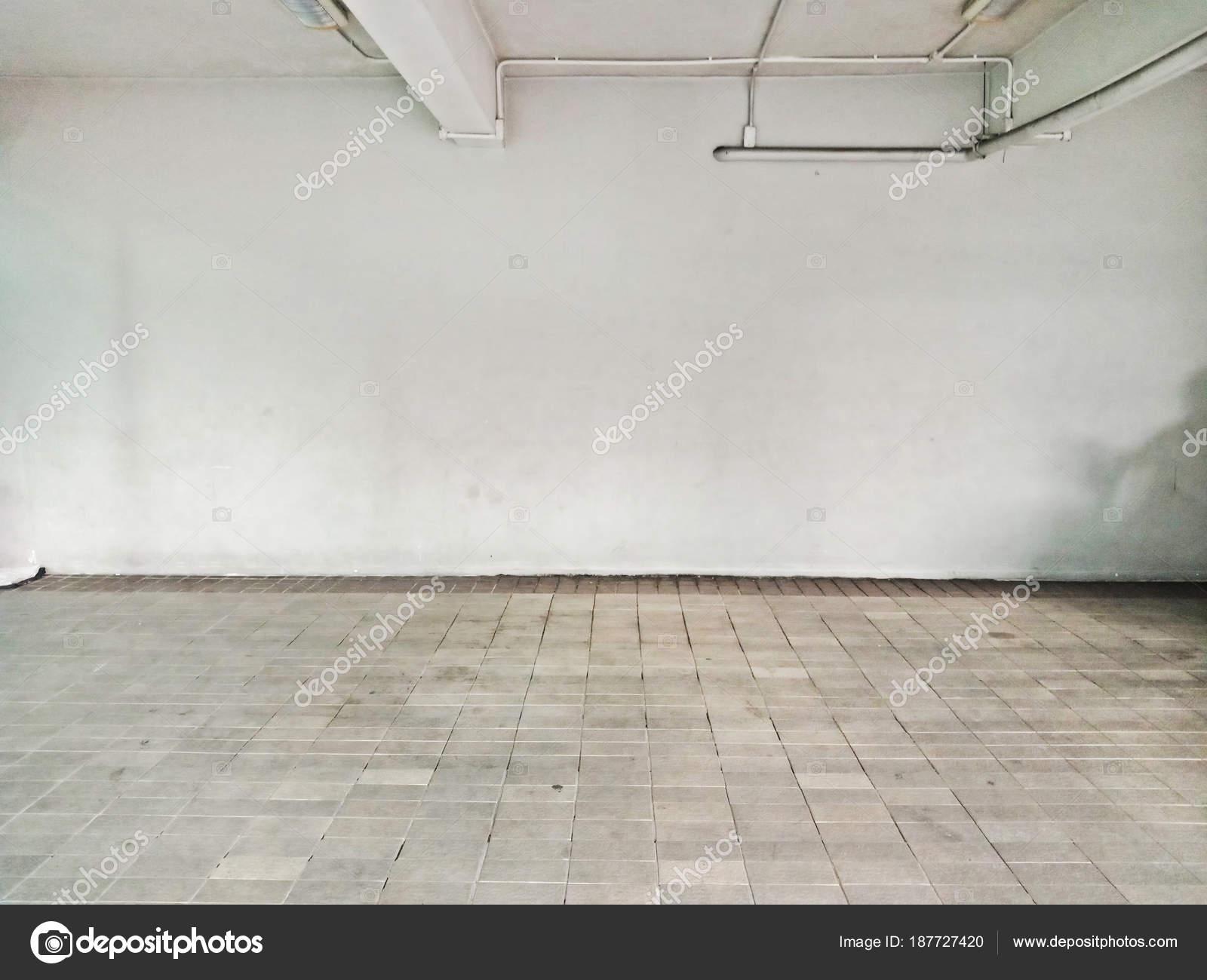 Parcheggio al coperto vuoto con il pavimento di mattoni di cemento ...