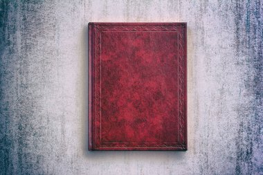 the book in a red cover over gray grunge background, top view with vignette