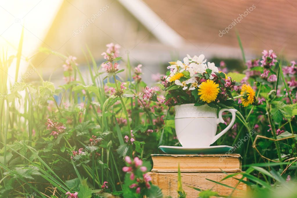 rural landscape a stack of old books with a glass of flowers on a background of flowering grass and a rustic house on a spring or summer sunny morning
