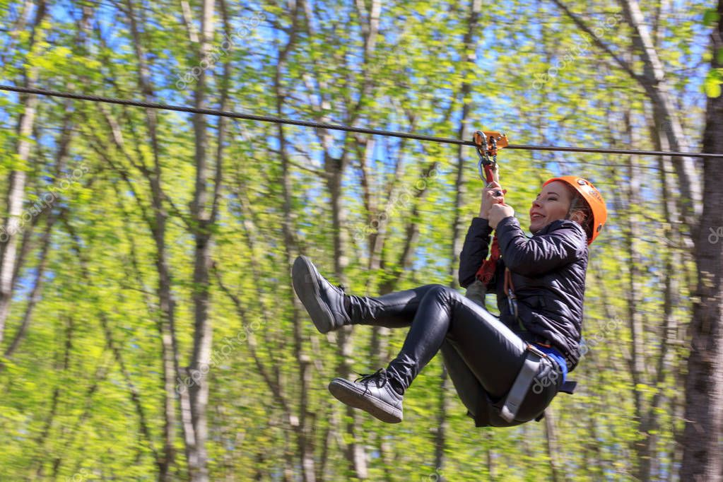 Adygea, Russia - April 15, 2018: cheerful young tourist girl descends on Zipline