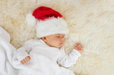 Baby sleeping with Christmas hat on