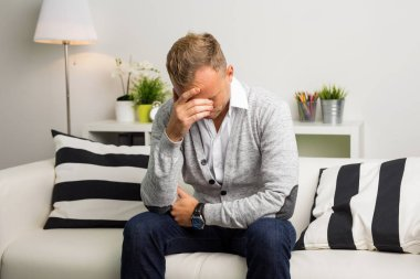 Depressed man sitting on the couch