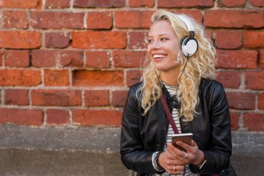 Happy hipster with headphones listening to music