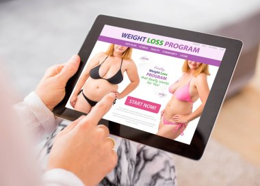 Woman reading about weight loss on tablet computer