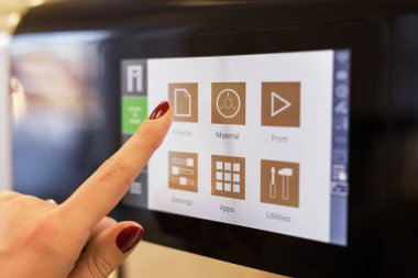 Person using 3D printers touch screen