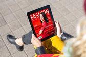Žena čtení módní časopis na tabletu