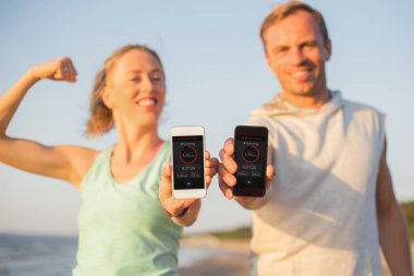 Couple using fitness app on their mobile phones