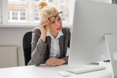 Woman at the office looking at computer with her eyes squeezed