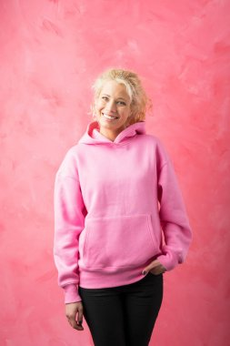 Woman wearing pink sweatshirt  on pink background