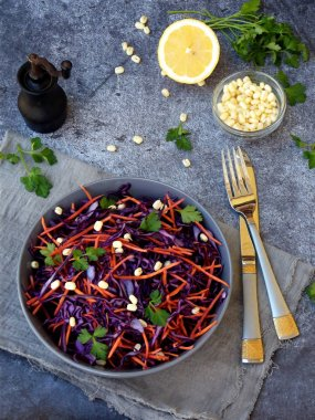 Fresh vegetables salad with purple cabbage, carrot, sprouted mung, parsley on grey clay plate on dark background. Cole Slaw Salad of red cabbage. Top view.