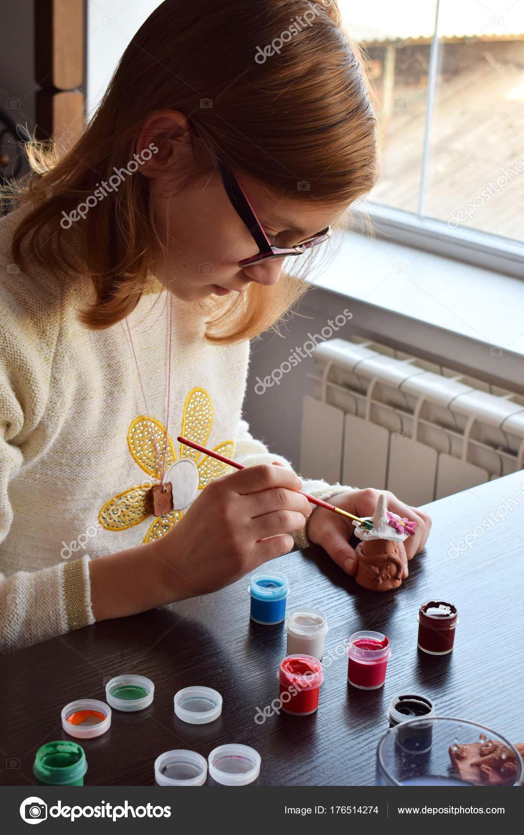 fille de fabrication de jouets bricolage, peint un jouet d'argile de