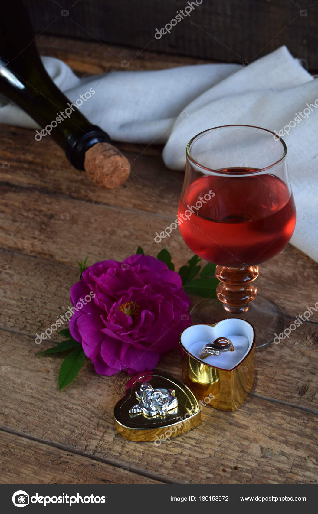 A Glass Of Red Wine Bottle Rose And Ring On Rustic Wood Table