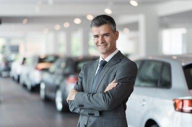 Confident car salesman at the showroom