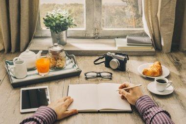 Hipster man writing a journal