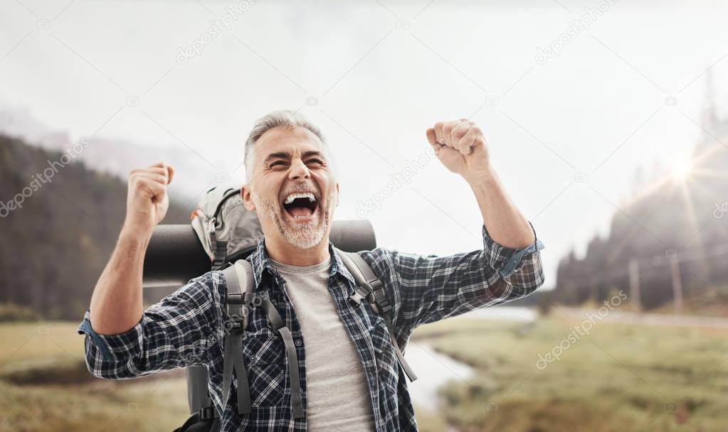 Cheerful hiker celebrating with raised fists