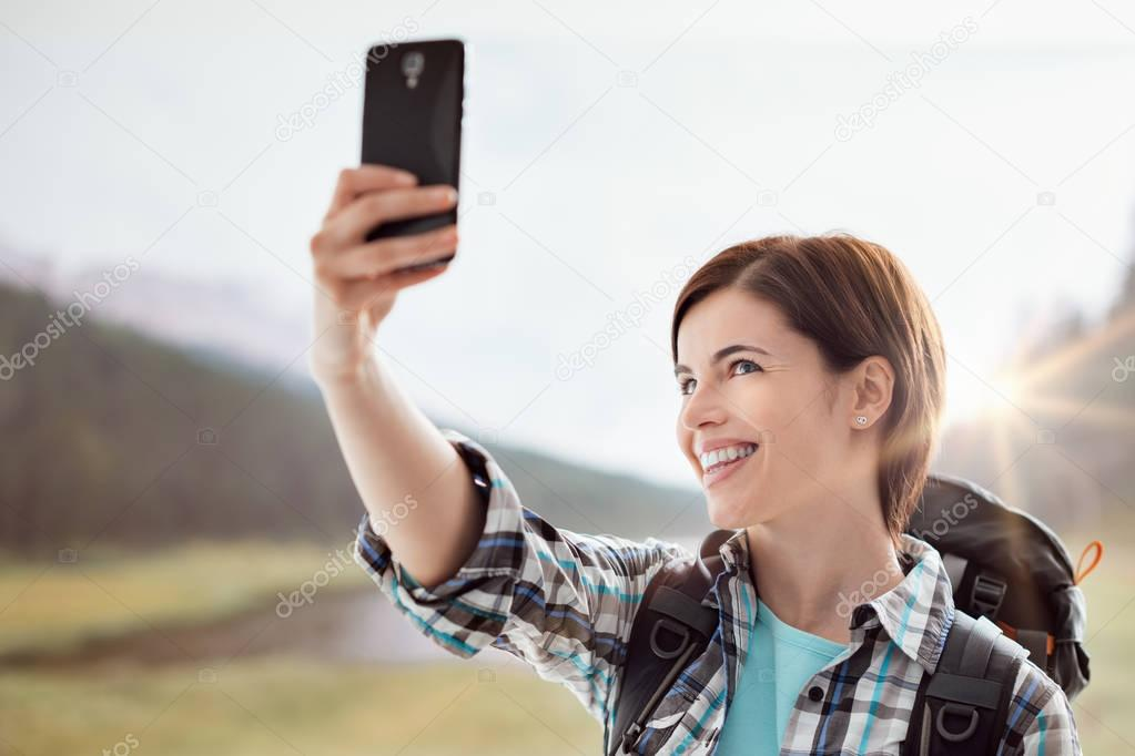 Hiker taking pictures with a smartphone