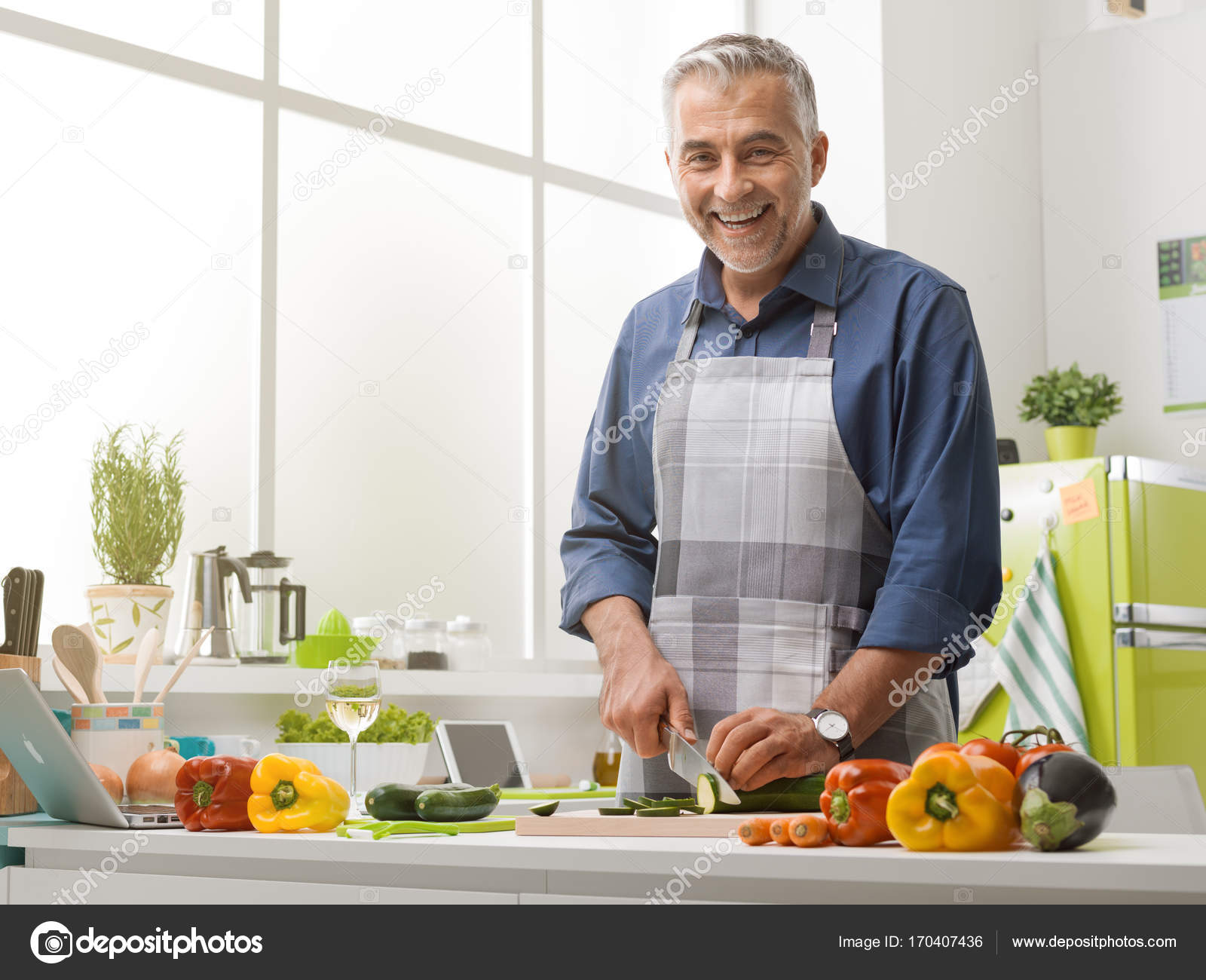Happy man cooking in the kitchen — Stock Photo © stockasso #170407436
