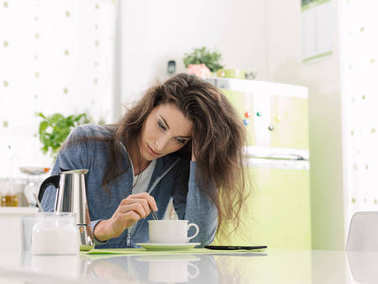 Tired woman having breakfast at home
