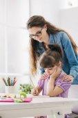Fényképek Anya és gyermeke csinál házi feladatot együtt