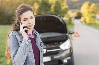 Woman calling car assistance