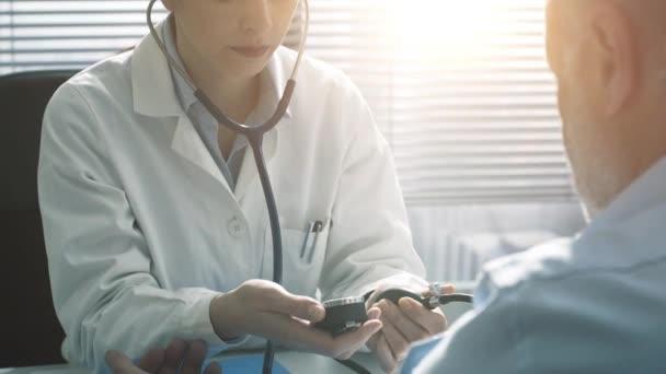 Ärztin misst Blutdruck einer Patientin