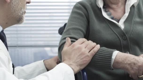Arzt tröstet Seniorin im Rollstuhl