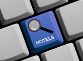 Nagyító ikon a kék számítógép billentyűzetén - Hotelek keresése