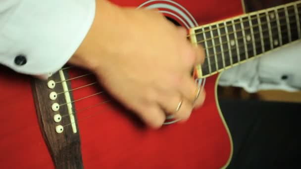 Guitarist playing on six-string acoustic guitar